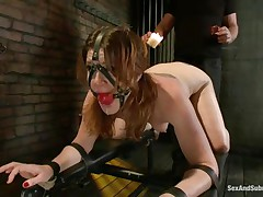 Cici Rhodes likes the dungeon. Belted to a board, tied and gagged the brunette receives a punishment with sexy wax and spanking. Her slaver removes a metal plug from her ass, then re-inserts it, attaching a rope from it to her head. A vibrator runs over her pussy, making her want to cum, but can't yet.