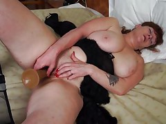 She's mature, hot and has a pair of immense scoops that need a hard penis between them. Meet Leah, a plump older whore that's masturbating in front of us. Leah uses her big bad dildo to fill her pussy and has a great time doing it. The wet crack rubs her scoops while masturbating and groans with delight wishing for a real 10-Pounder