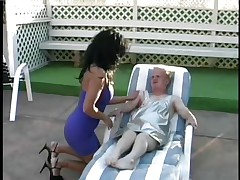 Meet Joey the Midget, the fortunate dwarf who gets his shlong wrapped by the lips of that hot brunette chick Lamia. See how this babe is treating his hard large cock and engulfing it with all her heart as Joey is lying on that chair by the swimming area. Licking, jerking and engulfing really makes Joey happy.