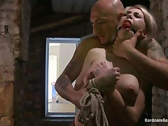 This sexy blonde babe, Isabella Clark, receives abducted by a bald chap and taken to a quiet place. Her mouth is ball gagged and she is completely naked! The chap tied her on a ottoman and left her there. After a while, a chap comes in and starts teasing her with his cock and fucks her from behind
