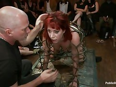 They've putted her in a special cage and as the bald guy fucks her sexy mouth, 3 dirty strumpets are taking worthy care of her ass. She is fucked from one as well as the other ends and the sex toy and fingering she's getting on her a-hole only makes her mouth desire to swallow that dick as deep as she can while the public see her.