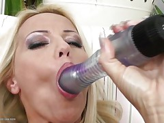 Blond milf wearing only a couple of hot black nylons is playing solo with her large dildo, that babe sucks it and the fills her shaved wet crack with it, fucking herself as hard as that babe can but that is not enough. Luckily her brunette girlfriend is willing to aid and gives her a hand, rubbing her muff and then fingering it, desire to see what else she's willing to do?
