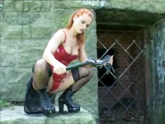 Beauty in leather with a flogger outdoors