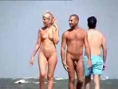 Nude couple filmed walking along the beach, nice blond with cute tits and shaved pussy.
