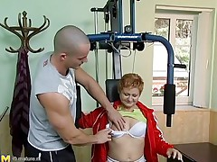Watch this hawt red headed cougar who takes advantage of this young gym instructor. She has great sex experience and begins seducing him, like she well knows. This old babe has all she needs to make a man happy. She begins taking off her clothing to turn the young stud on. He likes playing with her tits.