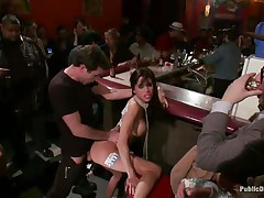 Gia DiMarco is on a rope leash, getting fucked in the wazoo right in the centre of the bar while the patrons watch. This babe continuously thanks James Deen for fucking her ass. Then she's on the floor, getting fingered by a woman, squirting all over. This babe mops up the mess with Gia's hair, then fists her.